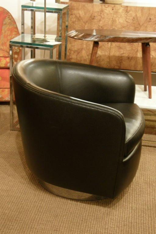 A pair of chic barrel back swivel and tilt lounge chairs upholstered in black leather raised on a round chromed steel plinth by Milo Baughman for Thayer Coggin, American, circa 1970.