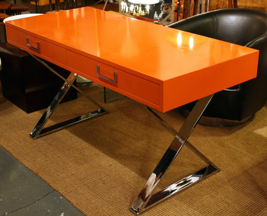 A chic vibrant orange lacquered campaign desk with two drawers, raised on X form polished chrome plated steel legs. By Milo Baughman. American, circa 1975.  Please call gallery for details, availability and item location.