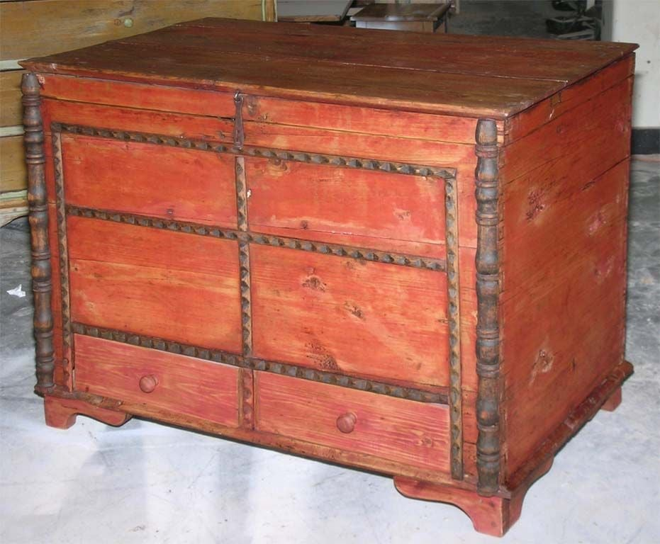 Charming country chest in red paint with turned columns and carved mouldings. Has interior candle box and two large drawers below.