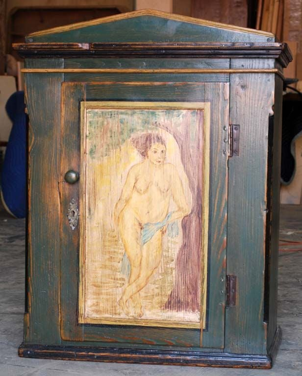 This wall cabinet painted with kitschy nude has a wrought iron hanging loop but can also stand on the floor. The original lock is intact.
