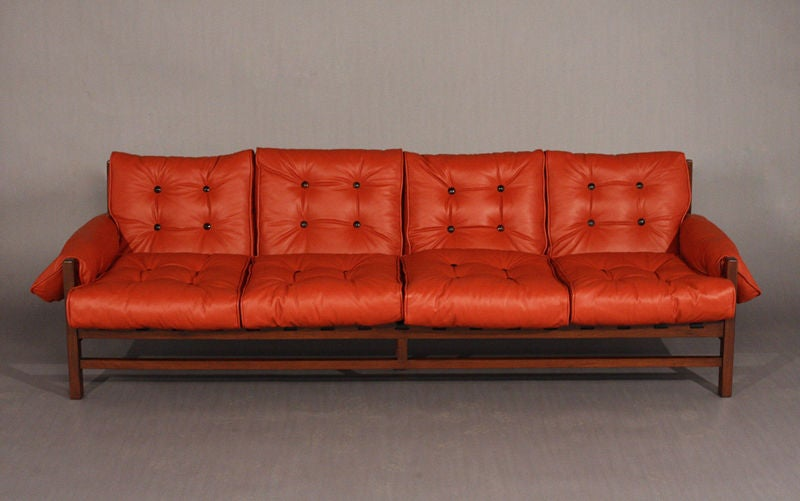A Rosewood And Red Leather Sofa With Black Pigskin Straps