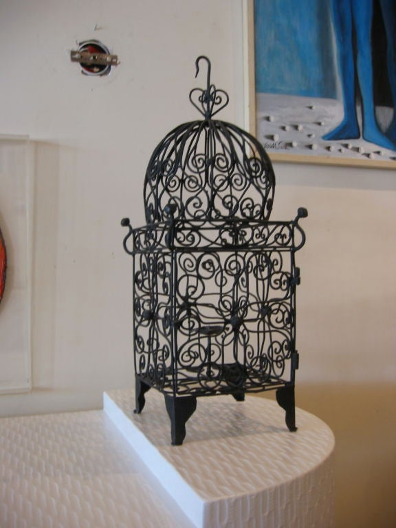 This iron candle lantern fashioned in curly iron is slightly Moorish in style. It has a latched door and iron hook for hanging. Stands on four legs as well. Great as a candle lantern for many different room styles or in a garden. This will be a