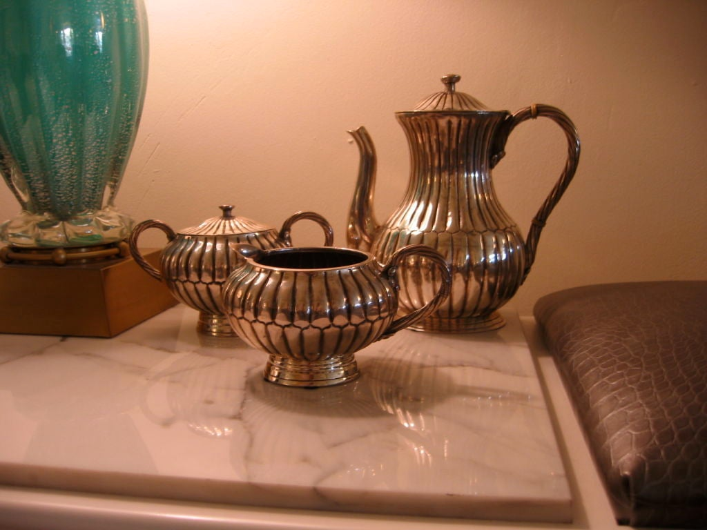 Sterling tea and coffee service set consisting of tea pot, creamer, and covered sugar bowl. Ribbed design on each piece and all handles are rope design. Two bakelite rings embellish the sterling roped handle of the tea/coffee pot. Each piece is