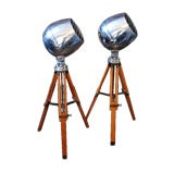 Pair of polished aluminum industrial spotlights on tripods