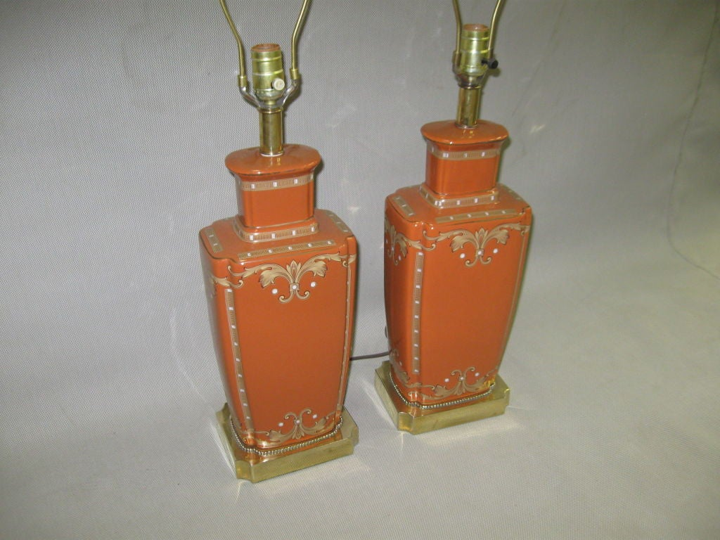 PAIR OF RECTANGULAR ORANGE CERAMIC AND GOLD DETAIL TABLE LAMPS WITH BRASS BASE.