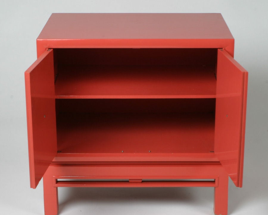 Pair of Coral lacquer nightstands or small cabinets with brass pulls and inset handles, in the manner of Tommi Parzinger.