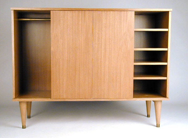 Edward Wormley cabinet, center drawers with inset handles, shelves on right side of sliding doors and a hang bar on the left side. Bleached mahogany. Sale price $1800.