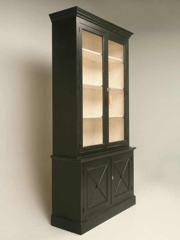 Handmade reproduction bookcase in the Directoire style with a black hand-brushed. The interior is a French vanilla color and imported French chicken wire is placed in the upper doors (wood, glass etc. optional.) You can spec your own dimensions and