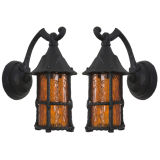 A pair of painted iron and amber glass exterior lanterns