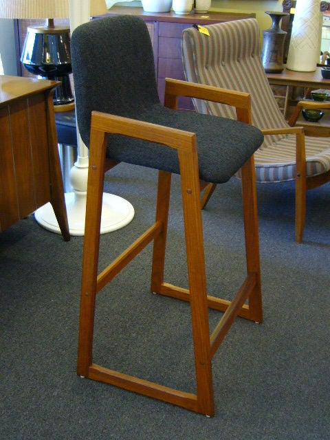 Beautiful pair of Danish Modern scoop seat bar stools with solid teak frame. This is a pair with a unique angular design with legs rising up to form arms. Sturdy and strong, solid. New woven fabric over foamed bentwood forms. Fabric is dark charcoal