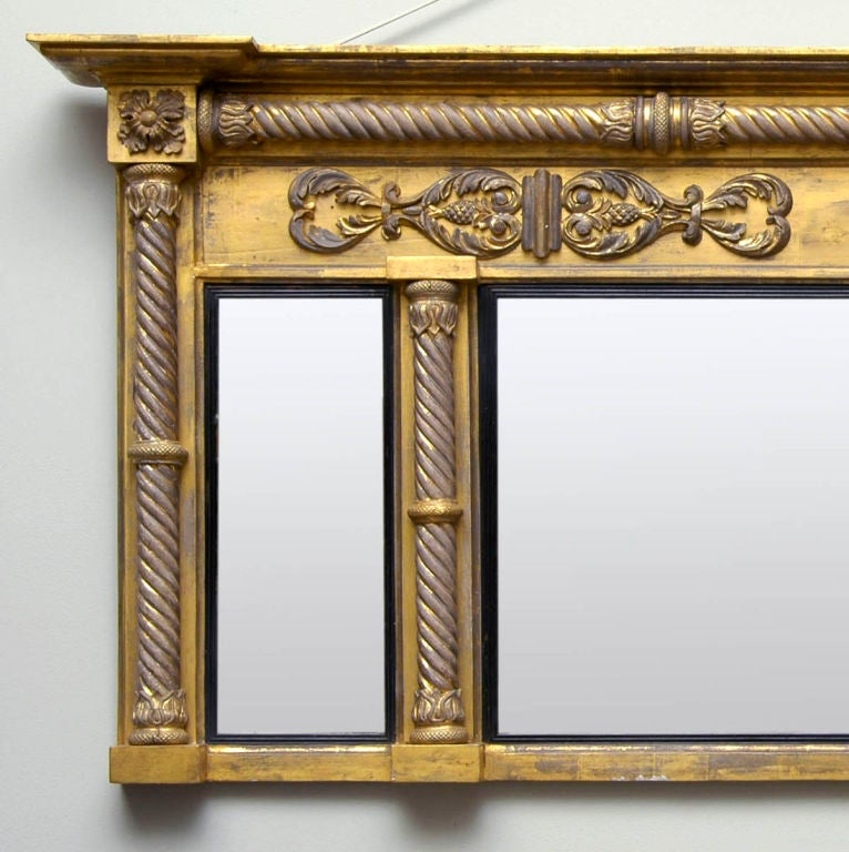 Regency giltwood overmantel mirror with breakfront molded cornice set above a horizontal spiral column and frieze with carved pineapple and foliate mounts, central rectangular mirror plate flanked by smaller plates, all with ebonized reeded slip,