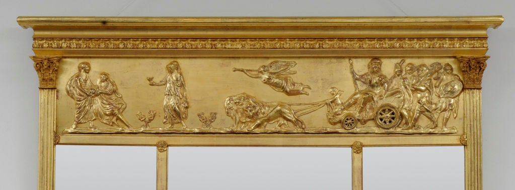 Victorian giltwood overmantel mirror with three beveled mirror plates, a frieze with applied classical decoration of lions pulling a chariot, soldiers, putti and muses below molded cornice, reeded flat columns topped by Corinthian capitals.