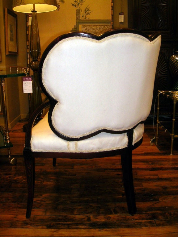 A mirrored pair of generously proportioned French Art Deco mahogany framed chairs, the back of curved leaf form upholstered to simulate veins, the stem forming a single arm with upholstered seat resting on two carved squared, tapered front legs and