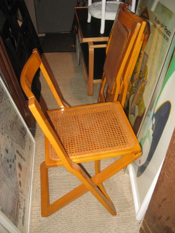 Set of four Mid-Century cane and laquered wood Italian folding chairs.