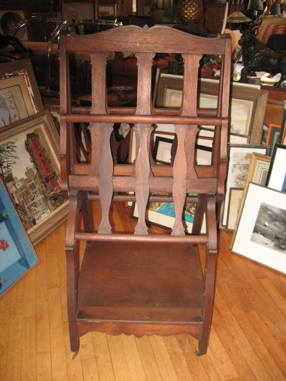 "Late 19th century walnut folio stand with under shelve and wooden wheels. Measures: 48"" open."