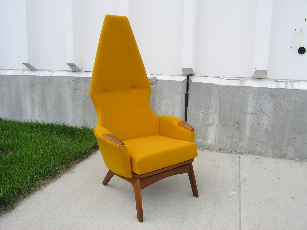 The dramatic form of Adrian Pearsall's angular chair, model 2056-C, belies its comfortableness. With a towering back and stylized walnut frame and armrests, it will be a focal point in any setting.  The chair has been expertly reupholstered in