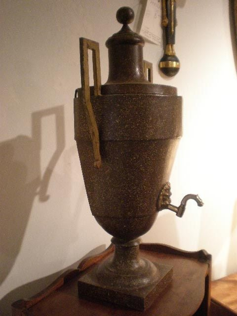 Tole urn with handles and brass spout with lion head detail.