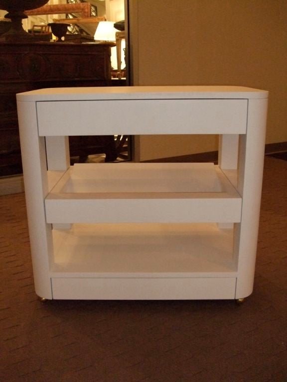 A three-tiered custom-made bedside book table designed by Charles Spada. The middle shelf is angled to house books so their spines can face out. They come in a white primer finish.