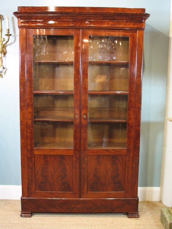 French flame mahogany bookcase, period Louis Philippe, with French polish finish, containing four shelves with mahogany-veneered edges, glass-front double doors, and one locking key.