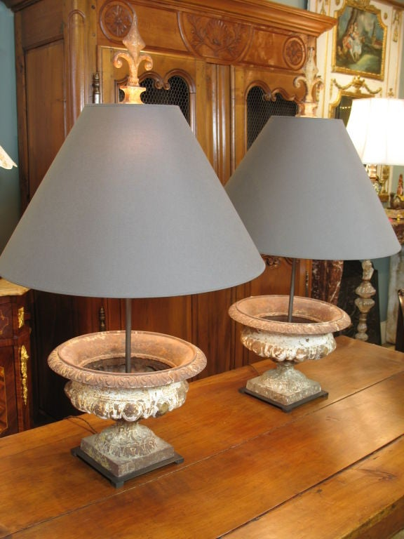 Pair of French, 19th century cast-iron urns in the neoclassical manner, newly-mounted as lamps, with cast-iron finials, and new paper shades. The overall height to the top of the finial is adjustable, but 41