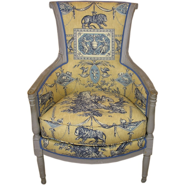French Directoire period blue-gray painted bergere, newly-upholstered in lovely blue and gold toile fabric based on a museum-archived pattern. Very pure neoclassical detailing and form.