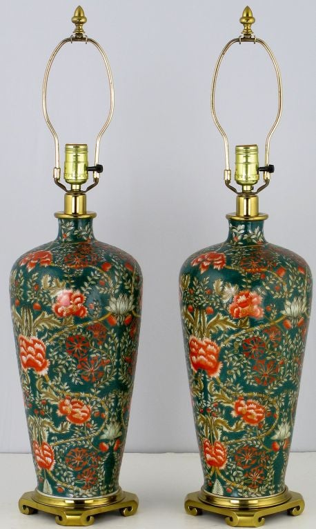 Evoking the Arts and Crafts nature themes of William Morris, this outstanding pair of table lamps are grounded by a heavy brass base in a stylized Asian form. The deep teal green ceramic body is decorated with hand painted coral, red, white and gold