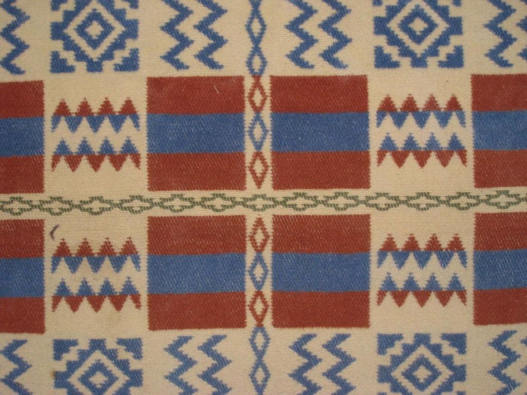 Crisp geometric design with blue, rust and beige.  Ends bound in green.