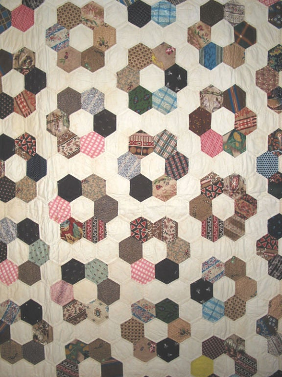 Extraordinary fabrics cut into hexagons and pieced together form this elegant spread. Probably made by Mrs. O.E. Bishop,