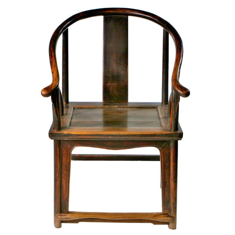 """Rare late 18th century Chinese horseshoe armchair with curving top rail connected with """"pipe joints"""" and ending in out swept arms. Features simple curved back splat and legs joined with step stretchers. This chair demonstrates superb Chinese"""