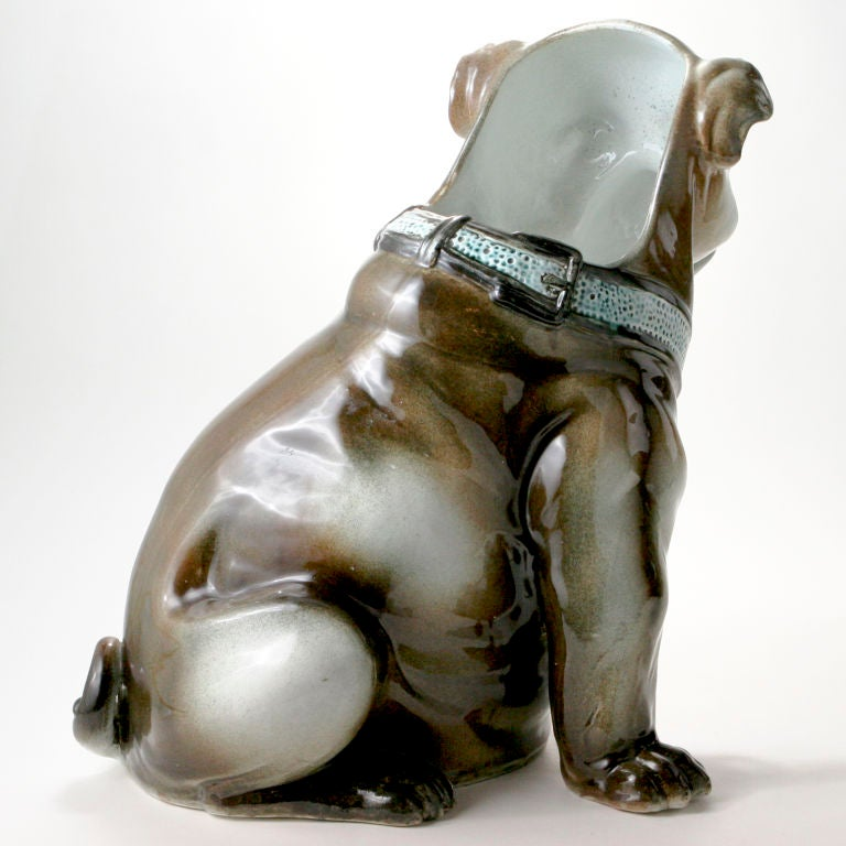 Life-size Belgium ceramic bull dog in tan, brown and cream colors with blue eyes complimenting blue and gold collar with large gold hoop. Back of dog open for use as umbrella or stick stand. Signed by the pottery: Mouzin Pottery, Wasmuel, Belgium &