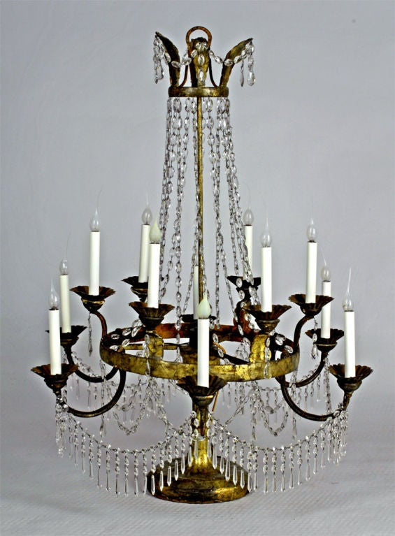 A pair of Italian crystal, iron and giltwood table chandeliers, 18th century, surmounted by the top tier with gilt leaf sprays issuing crystal drops with chains of crystals leading to a graduated tier with 12 alternating iron C-scrolled arms and