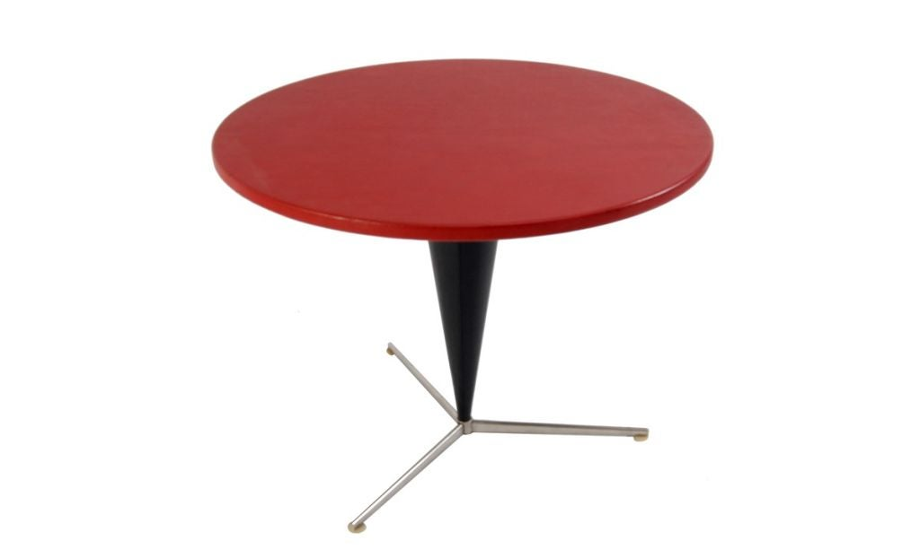 Rare cone dining table with red leather top and black vinyl upholstered metal pedestal on three feet with white plastic glides. Made by Plus Linje.