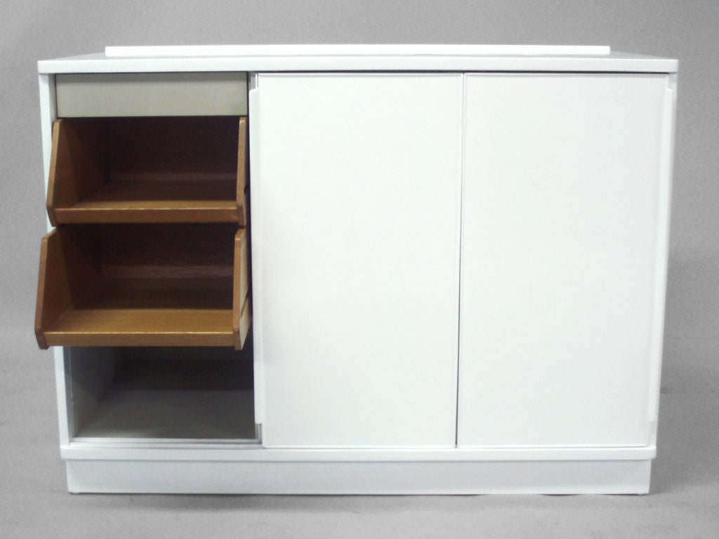 A white lacquered sliding door cabinet by edward wormley for Kitchen cabinets with sliding doors