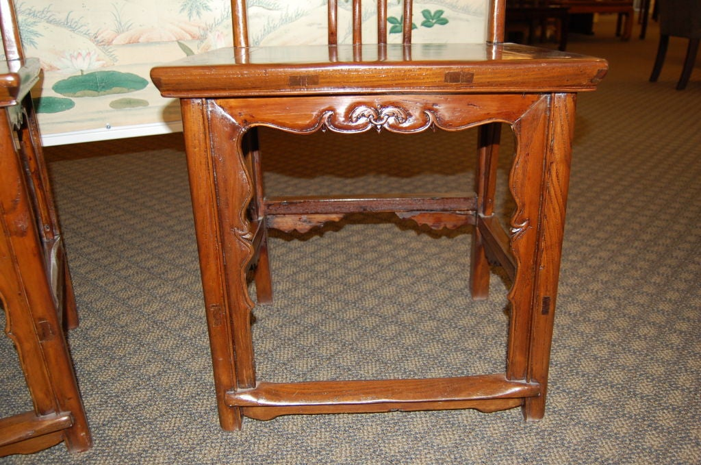 A pair of Chinese 18th century wooden side chairs made of elmwood. With graceful lines, and carving.  Measure: Seat height is 21 inches.