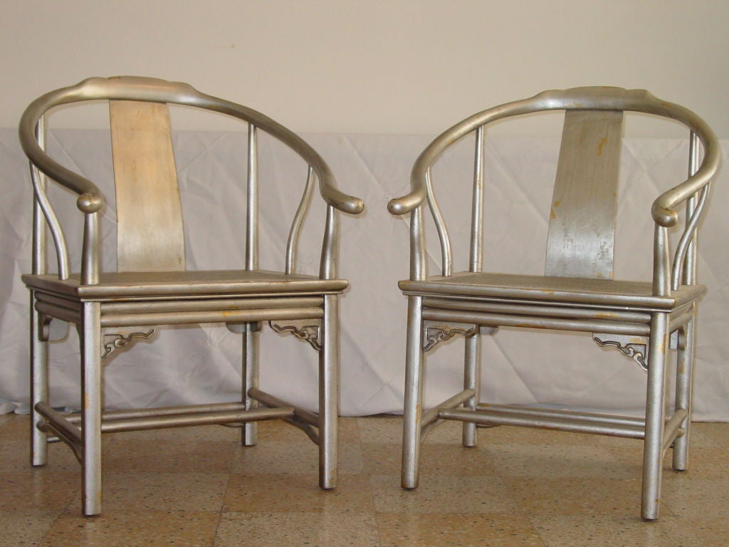 Pair of Asian inspired chairs in silver leaf with random patches of gold.  Cane seats in excellent shape.  Very much in the manner of James Mont, both in design and finish.  Two pair available.