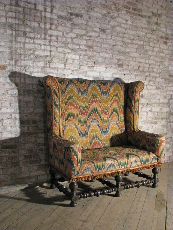 Italian settee with a bold presence and unusual design, high back and strong, turned base, antique flame stitch fabric.