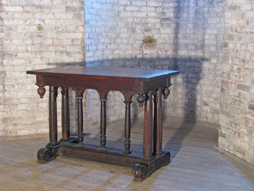 Decorative small center table of typical renaissance design, 19th century, incorporating earlier elements. The rectangular top supported by seven fluted columns ending in a H-form carved stretcher.