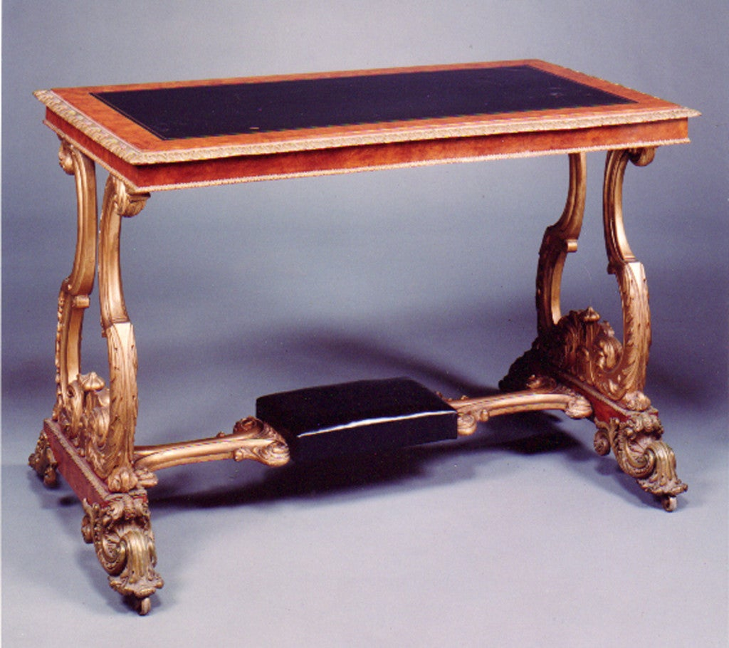 Elegant William IV writing table, top with an inset black leather and writing surface and gilt bronze edge, on a giltwood base with a black leather foot rest and elaborate gilt bronze feet and casters. (After a design published by John C. Loudon in