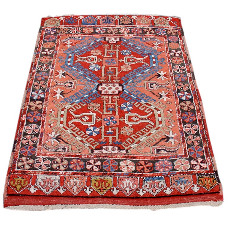This rug with a distinctive apricot field is from the area around Konya in central Anatolia. Its thick wool and larger knots may indicate that it was woven as a sleeping rug or yatak. The colorful lappet ends reflect classical ottoman influence as