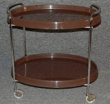 Modern bar/serving cart of dark brown molded plastic on a chrome frame with wheels.<br /> <br /> Pattern seen in photos in top tray is a reflection - all of the trays are very smooth, glossy and solid brown!