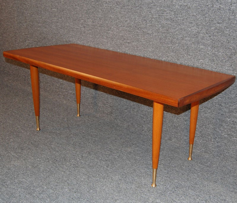 Sleek Coffee Table Of Rich Natural Teak Tapered Legs With Spun Brass Caps And Feet