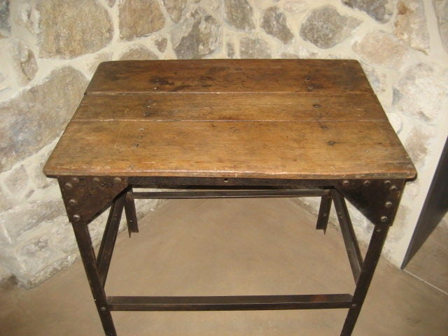 Vintage wooden table with riveted metal base.  See details for nuts and bolts and patina of base and table-top.