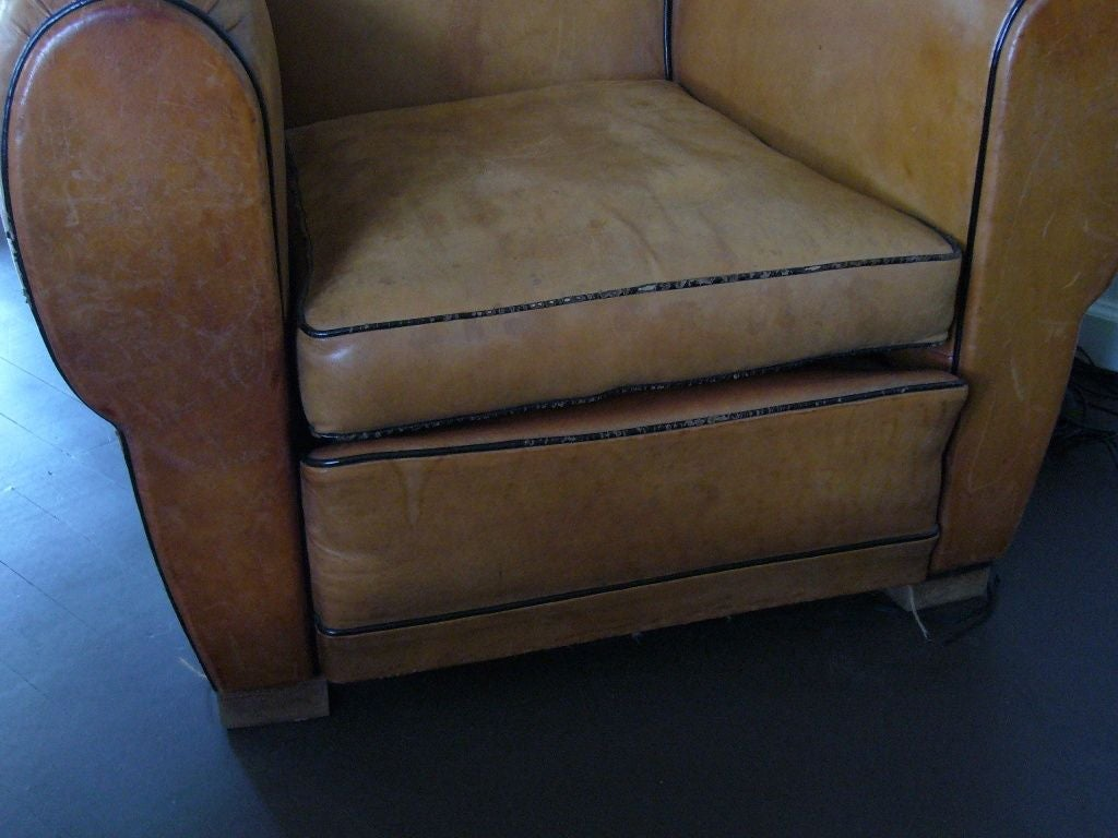 Pair of matching Art Deco club chairs. Tan leather with brown piping and wooden legs. Approx 1930-1940s.