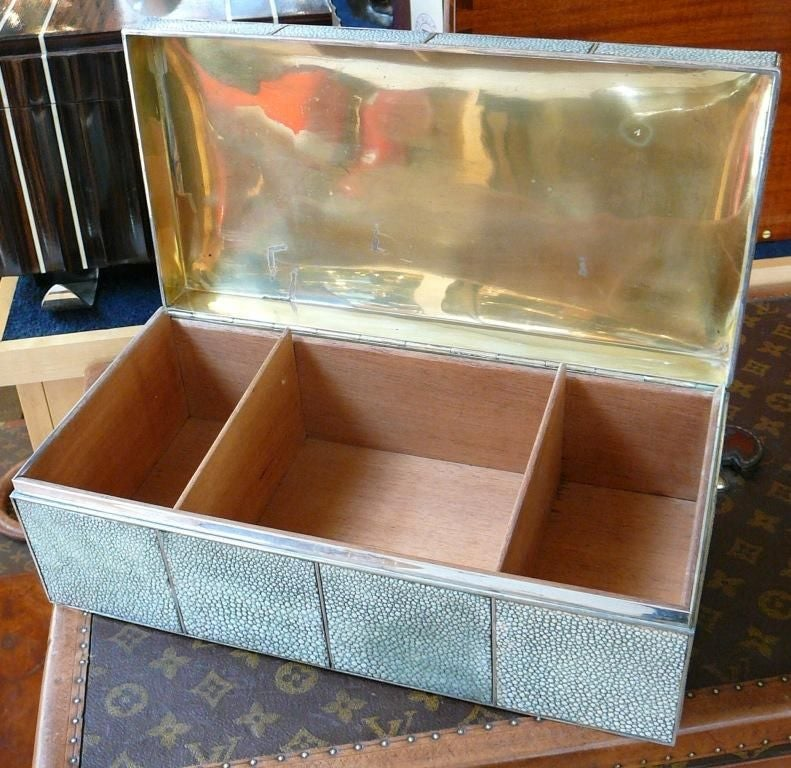 A Sterling silver cigar box of massive proportions, the facetted lid with shagreen panels and three silver faux 'cigars', with (unusually) the shagreen panelling covering all four sides of the box. The interior cedar-lined with two dividers, the lid