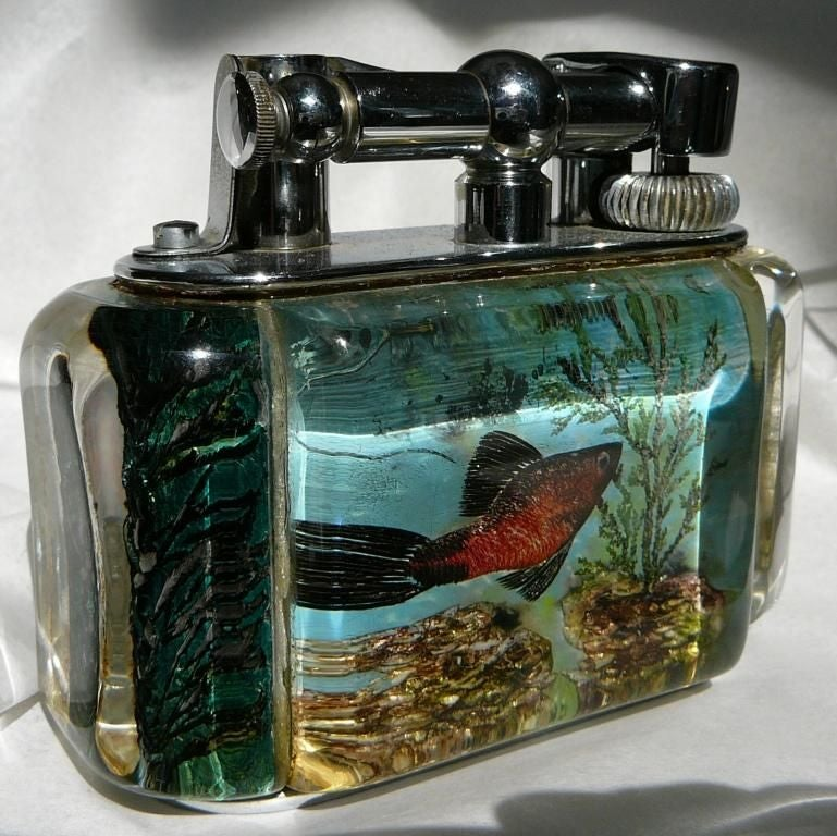 A silver-plated 'Aquarium' table lighter in 'Half-Giant' size, the perspex body enclosing decoration of fish, in pale blue-grey colour, and chrome plated lift-arm marked DUNHILL. <br /> <br /> <br /> <br /> Notes: The 'Aquarium' lighters were