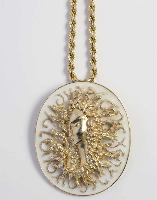 White enameled oval pendant with a crystal encrusted Medusa relief figure. Chain is Monet.