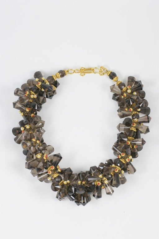 A smokey quarts pinecone necklace. Each smokey quartz drop bead is wire wrapped in 18kt yellow gold and has either a bezel set coral or peal bead at the end of each wire. There are 22kt yellow gold caps on either side of each round faceted smokey