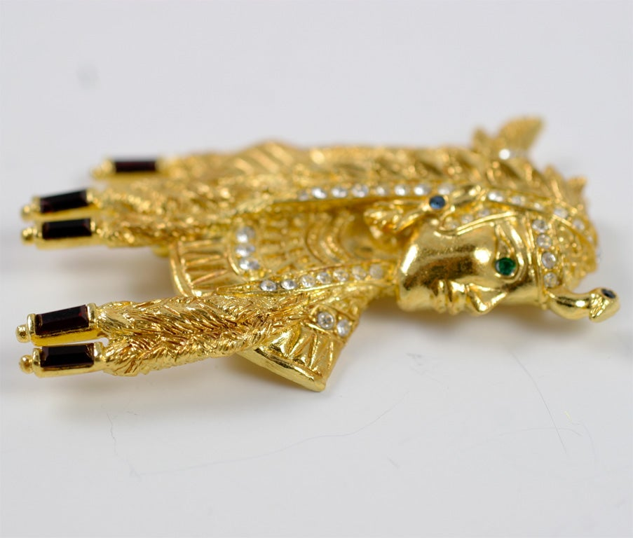 Gilt Cleopatra brooch with clear rhinestones and colored stones.