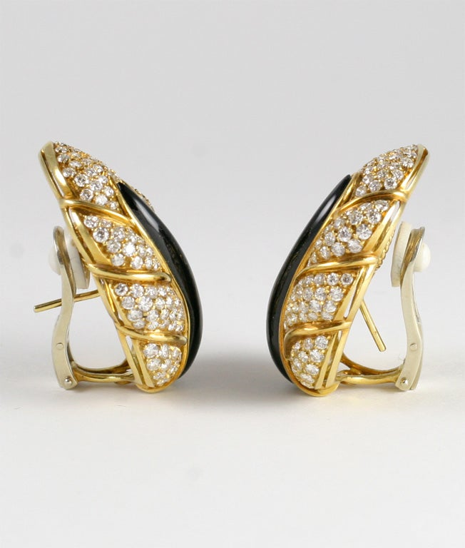 Pair of Large Leaf form earings , pave set with Diamonds. Approximately 8.5/9 cts of clean, full cut, white Diamonds, pave set. Center stem is carved onyx and leaves are segmented by 18kt Y.G. Ribs. Clip on.