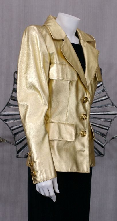 Iconic YSL Jacket in Gold kid leather with extreme pagoda shoulders circa 1986.  Gilt Bronze flowerhead buttons by Goosens. Black silk charmeuse lining. Crafted by YSL Haute Couture.  Iconic is an often used term. This jacket is testament to the
